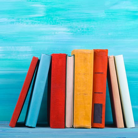 The spines of red, blue, yellow and white books on a bookshelf.