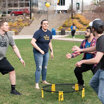 A group of college students playing a lawn game on the campus quad.