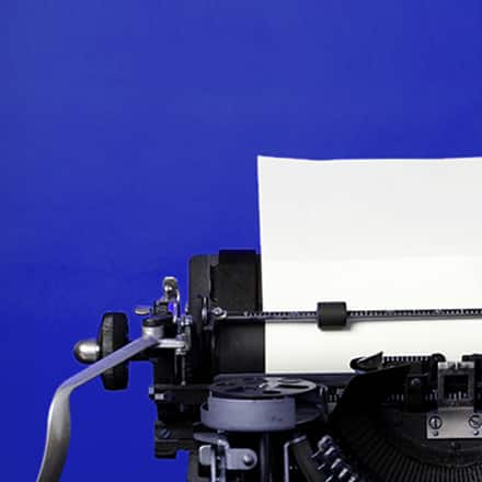 The upper left corner of an old fashioned typewriter with a blank sheet of paper loaded and clipped in place.