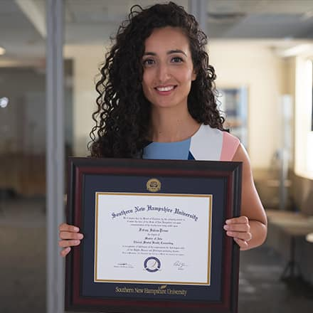 Fatma Salem Pease holding her framed master's degree from SNHU.