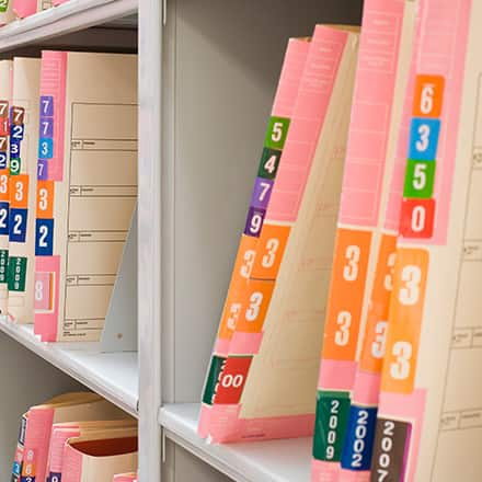 A shelf filled with medical files stored in manilla folders.