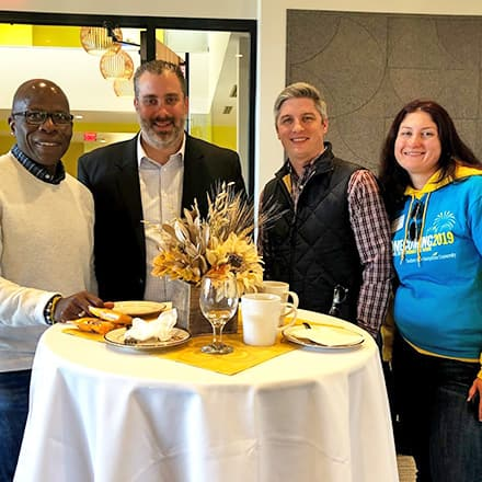 Three men and a woman standing at a round table during a reception held during SNHU's 2019 Homecoming weekend.
