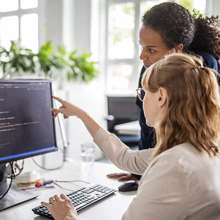 A woman points at a computer screen and gives advice on how to become a web developer