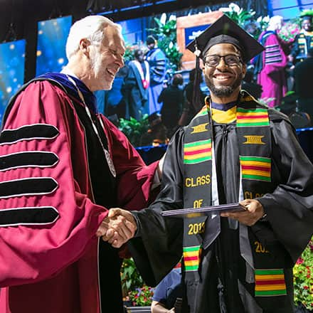A man in graduation cap and gown shaking hands with a university president as he receives his degree.