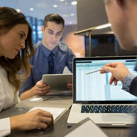 Three accountants pouring over data on a laptop screen.