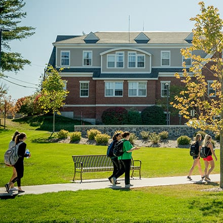 Students walking through a college quad on a sunny day.