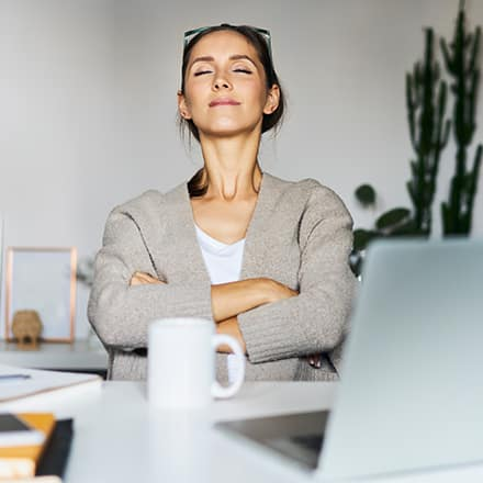 A woman sitting at her desk with her arms crossed and eyes closed practicing mindfulness meditation.