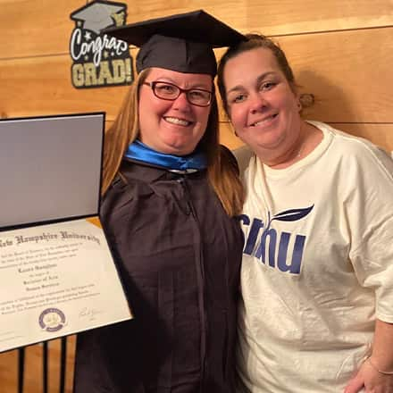 Laura Gaughan wearing her graduation cap and gown, holding her diploma and standing with wife Paula.