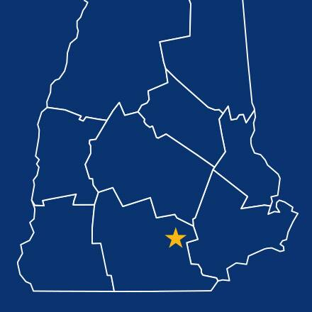 A blue map of New Hampshire with a yellow star denoting Manchester.