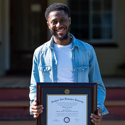 Matthew Seawright holding his degree from Southern New Hampshire University.