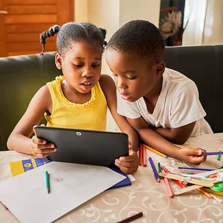 A sister and a brother using a tablet for remote learning.
