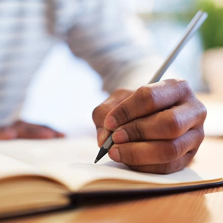 A man's hand holding a pencil and writing in an open notebook.