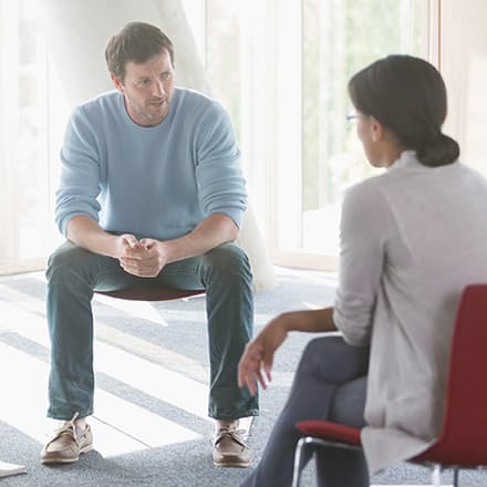A psychologist and client sitting in chairs during a therapy session.
