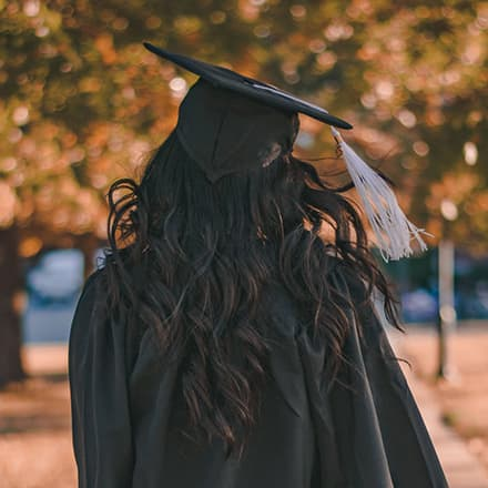 A student wearing a cap and gown walking away from the camera