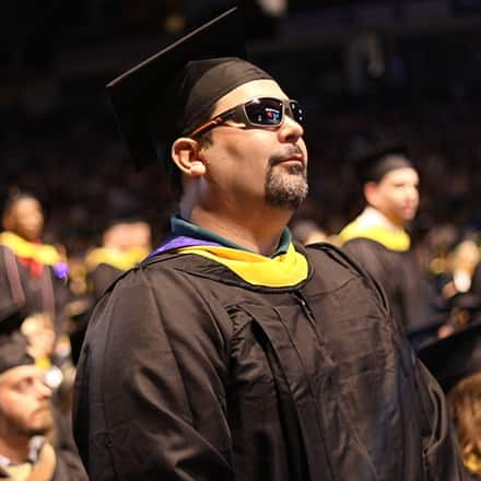 Ricardo Scarello wearing sunglasses and cap and gown at SNHU commencement ceremony.
