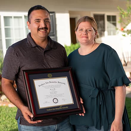 Sal and Shelly Villa in front of their home with Sal holding his framed diploma.