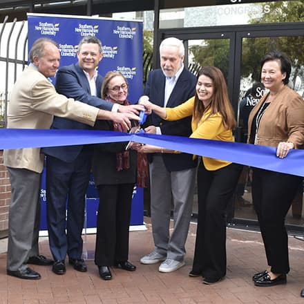 SNHU officials using huge scissors to cut a blue ribbon at the university's new southwest operations center in Tucson, Arizona.