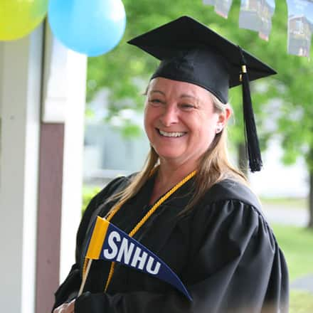 Fiona Mathiesen dressed in her cap and gown, holding an SNHU pennant.