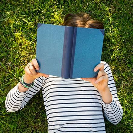 A person in a striped shirt laying in the grass with a blue, hardcover book blocking their face.