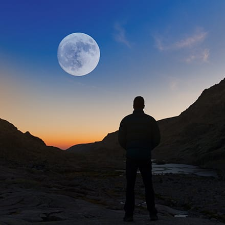 The silhouette of a man standing between two hills at dusk looking  at the moon.