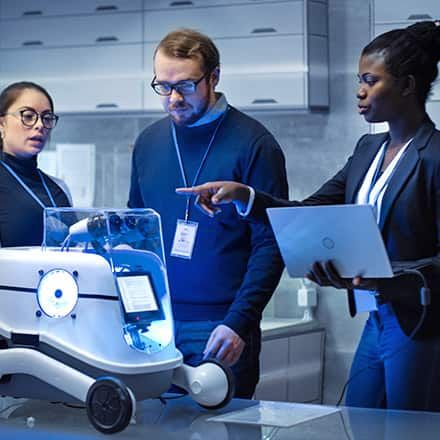 Three professionals working with a robot in a machine learning career.