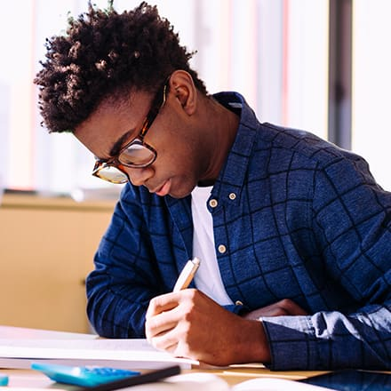 A man wearing glasses and a blue shirt studying for his associate degree.