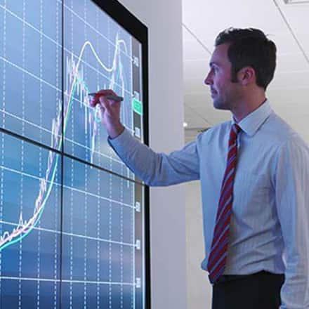 A finance professional studying a line graph on a large, wall-mounted computer monitor.