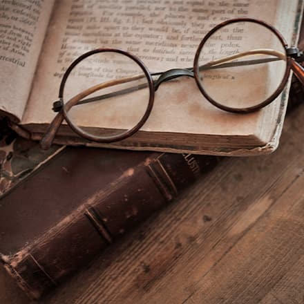 A pair of wire-rim glasses on top of an open book.