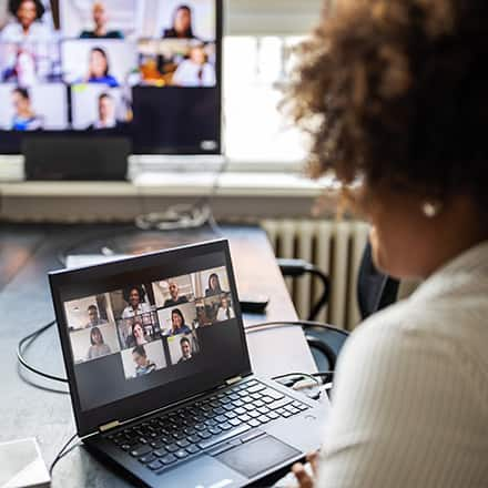 A woman looking at a group of her students on a laptop screen during the online portion of a blended learning experience.