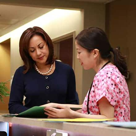 A nursing supervisor with her BSN talking with another nurse.