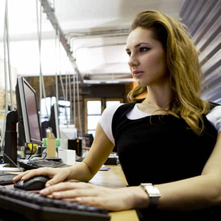 A female computer programmer working at a desktop computer.