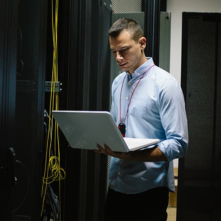 Man working as IT manager standing in a server room working on a laptop.
