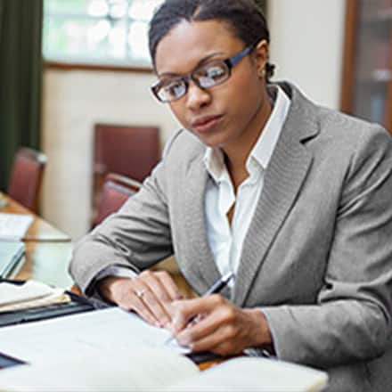 A woman in a business suit studying historical papers.