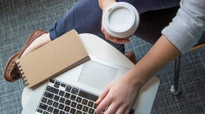 Person holding a cup of coffee while working on their laptop.