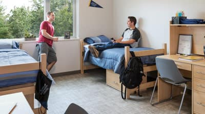Two students talking in their dorm room.
