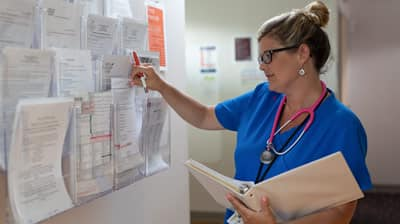 A nurse looking at medical documents.