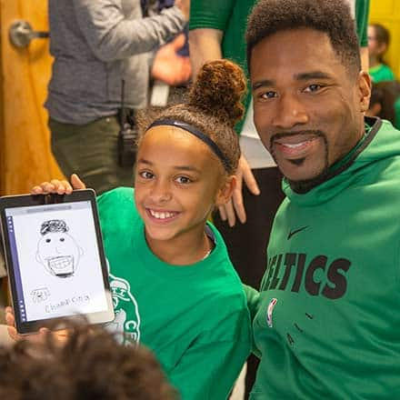 Former Celtics forward Leon Powe and a student who is showing off her work on a tablet
