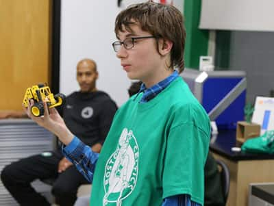 A student at Madeline English School showing the robot he assembled at the school's new technology lab.