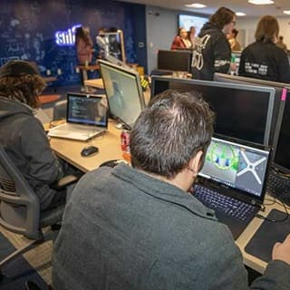 Group of SNHU students in SNHU's Inkwell Interactive Game Studio coding a video game