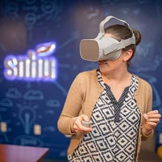 Woman playing a video game using a VR headset