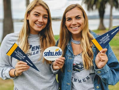 Photo of two women at SNHU homecoming holding SNHU sticker and pennants.