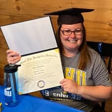 Laura Gaughan holding her SNHU diploma and wearing a graduation cap.