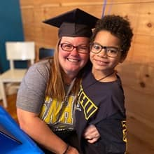 Laura Gaughan wearing her graduation cap and an SNHU shirt, hugging one of her sons who is also wearing an SNHU shirt.