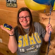 Laura Gaughan wearing an SNHU shirt, holding a miniature SNHU bus and balloons.