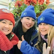Three female volunteers wearing hats posing in a picture together