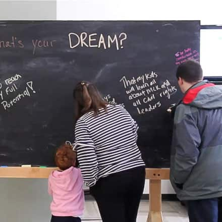 Attendee's of SNHU's MLK breakfast writing on a blackboard