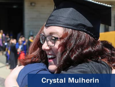 Crystal Mulherin wearing a cap and gown and hugging her academic advisor Brenda Matthews.