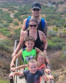 Heather Poss with her husband and three children on a mountain top hike