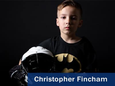 Photo of a boy holding a football helmet taken by Christopher Fincham.