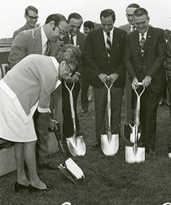 Gertrude Shaprio and a group of men in suits using shovels to break ground on SNHU's campus.
